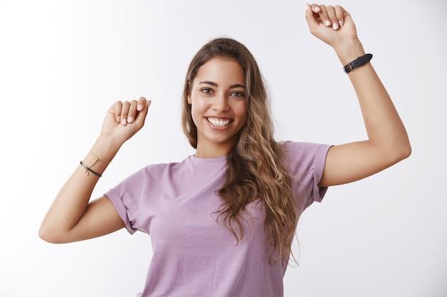 Fille exécutant la danse de la victoire. jeune femme séduisante charismatique enthousiaste levant les mains au rythme de la musique en mouvement célébrant l'objectif de réussite, souriant joyeusement, s'amusant
