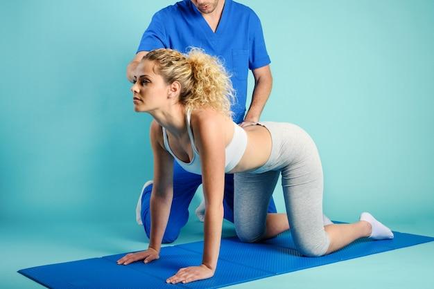 La fille exécute des exercices avec un physiothérapeute sur le cyan