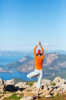 Fille exerçant le yoga sur un beau bord de mer
