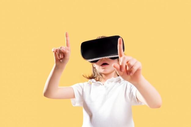 Fille expérimentant le jeu de casque vr en jaune. émotions surprises sur son visage. enfant utilisant un gadget de jeu pour la réalité virtuelle.