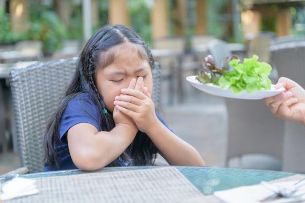Fille avec expression de dégoût contre les légumes