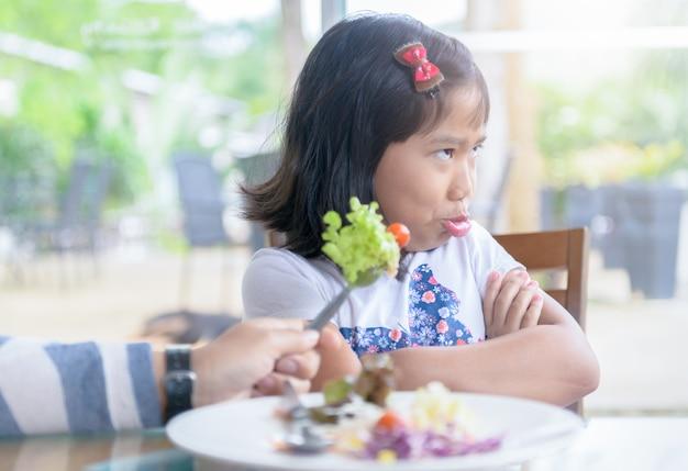 Fille avec une expression de dégoût contre les légumes