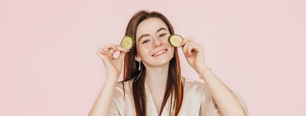 Une fille fabrique des masques de beauté pour le visage faits maison. concombres pour la fraîcheur de la peau autour des yeux. la femme prend soin d'une peau jeune. modèle riant et s'amusant au spa sur fond rose
