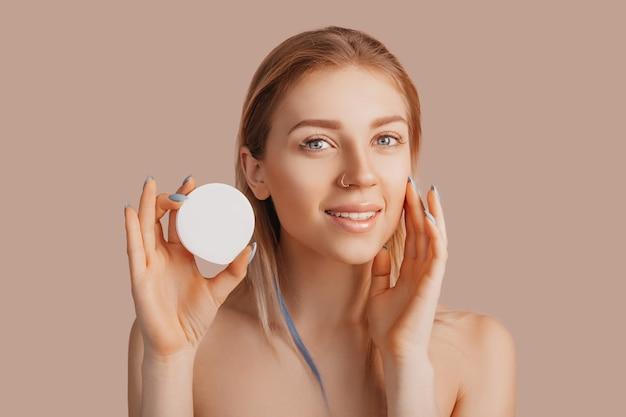 Fille faire des masques de beauté pour le visage. crème anti-rides pour la fraîcheur de la peau du contour des yeux. la femme prend soin d'une peau jeune. modèle riant et s'amusant au spa sur fond rose