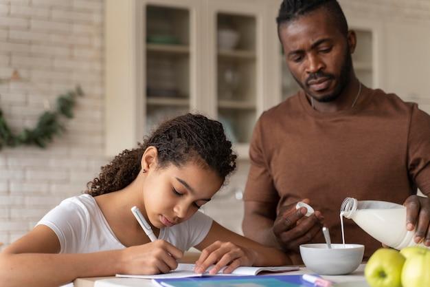 Fille à faire ses devoirs à côté de son père dans la cuisine