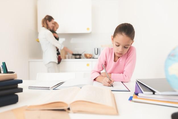 Fille à faire ses devoirs maman se tient derrière.