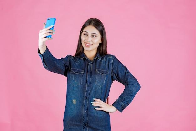 Fille faisant un appel vidéo ou prenant des selfies