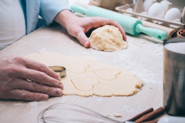 Fille faisant des biscuits en forme de coeur dans la cuisine, gros plan. surprise pour vos proches le jour de la saint-valentin, la fête des mères ou la fête des pères. contexte culinaire festif, avec amour.