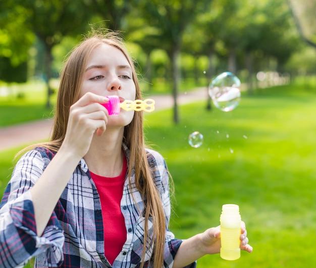 Fille faisant des bulles de savon à l'extérieur