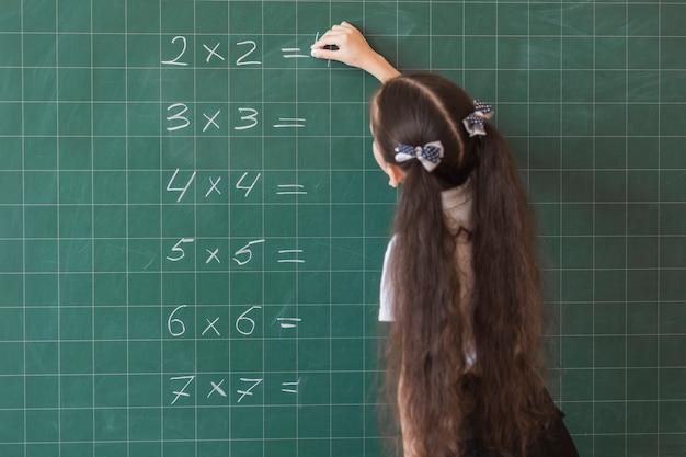 Fille faisant des calculs sur le tableau noir