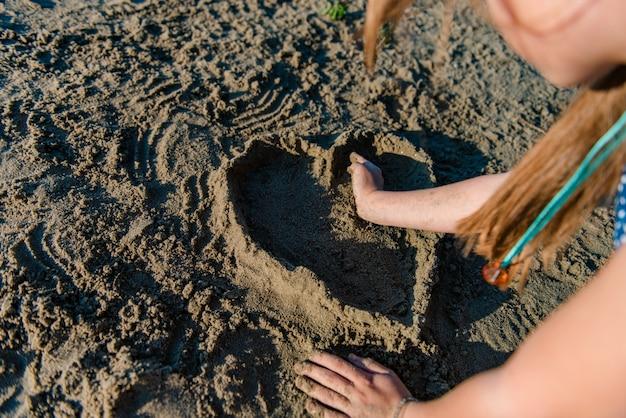 Fille faisant le coeur de sable