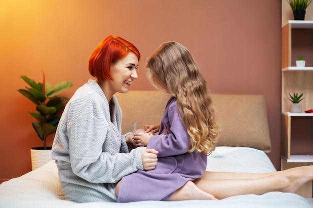 Fille faisant du maquillage mère, à la maison au lit