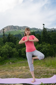 Fille faisant du yoga dans la nature sur fond de montagnes