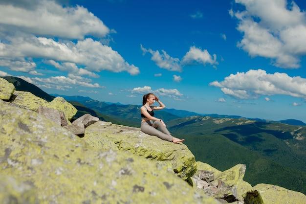 Fille faisant du yoga exercice lotus pose au sommet de la montagne.