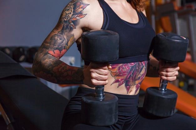 Fille faisant des exercices avec des haltères. fille avec des tatouages sur le fitness montre un beau corps avec des muscles. divers équipements sportifs et équipements de fitness pour le sport et le fitness