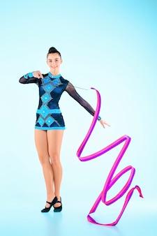 Fille faisant de la gymnastique danse avec ruban de couleur sur bleu