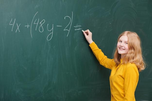 Une fille faisant des mathématiques sur un tableau noir