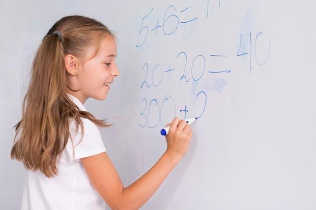 Fille faisant des maths sur un tableau blanc