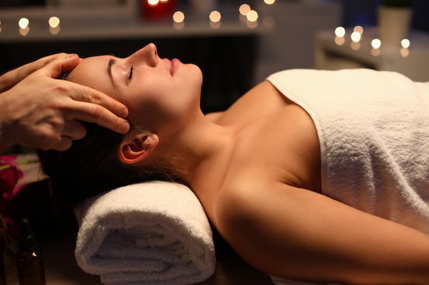 Fille faisant la relaxation massage de la tête dans un salon de beauté