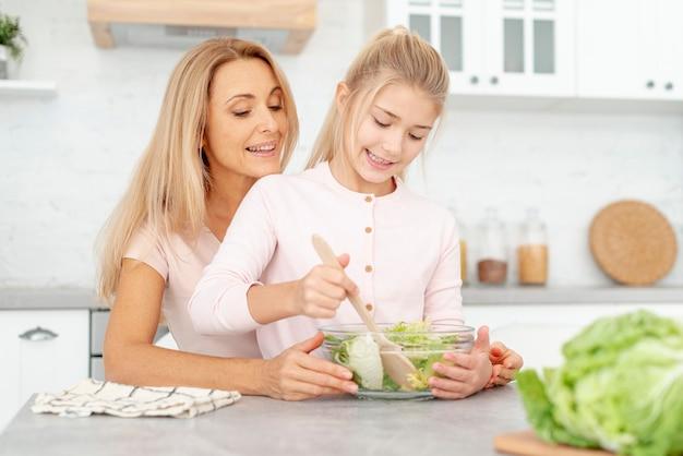 Fille faisant la salade avec sa maman