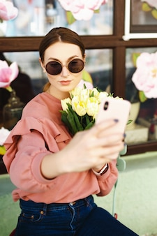 Fille faisant selfie avec tulipes