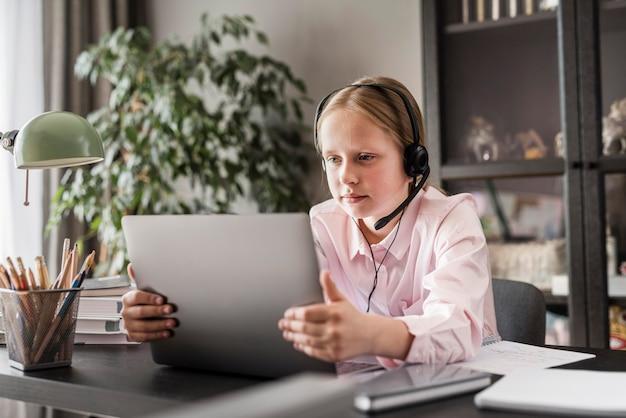 Fille faisant ses cours en ligne sur une tablette