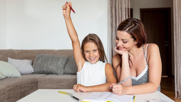 Fille faisant ses devoirs avec maman