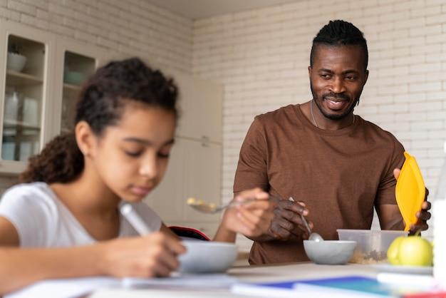 Fille faisant ses devoirs tout en prenant son petit déjeuner