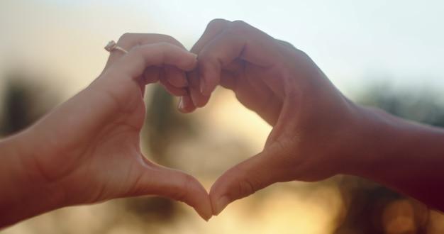 Fille faisant le symbole de l'amour avec ses mains contre un ciel doré magnifique et le soleil levant du matin