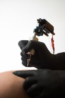 Fille faisant tatouage corps permanent jambe homme