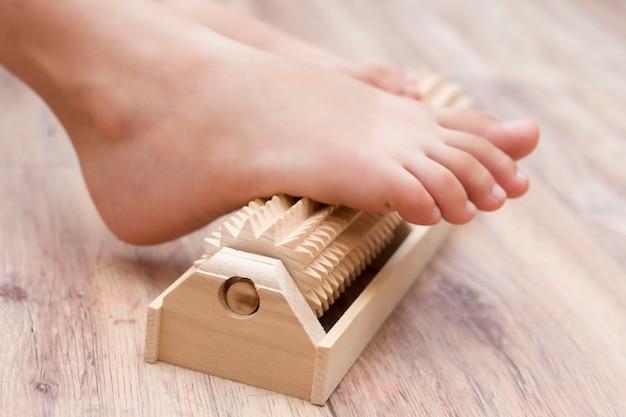 La fille fait un auto-massage des pieds sur un masseur spécial à aiguilles en bois pour la prévention des pieds plats, valgus. détente des jambes.