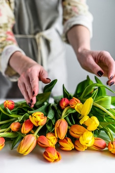 Une fille fait un bouquet de tulipes jaunes, orange et rouges