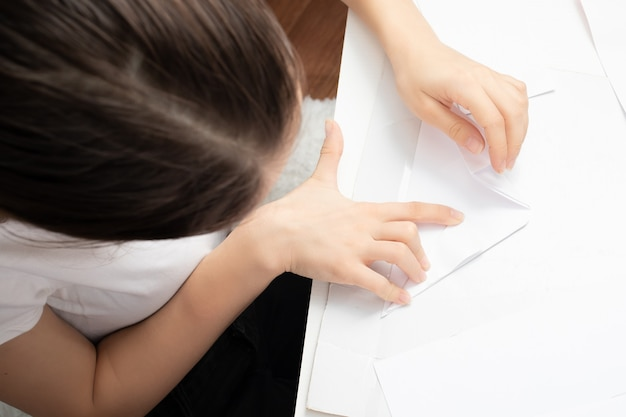 Fille fait des chiffres à partir de papier. concept de passe-temps