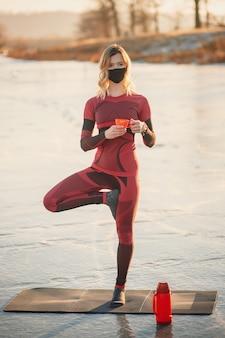 Une fille fait du yoga en hiver sur la glace du lac pendant le coucher du soleil