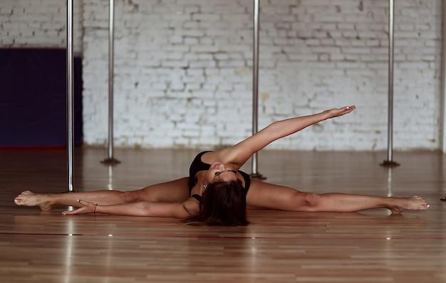 Une fille fait des étirements en faisant une jambe fendue sur le sol avant l'entraînement de pole dance