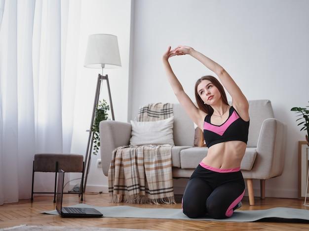 La fille fait des étirements à la maison. fitness à la maison