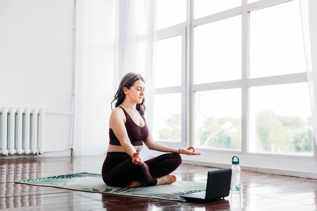 Fille fait des exercices, étirements, yoga, tapis près de la fenêtre, combinaison de yoga, corps, minceur et santé, exercices via internet, cours à distance, entraîneur informatique