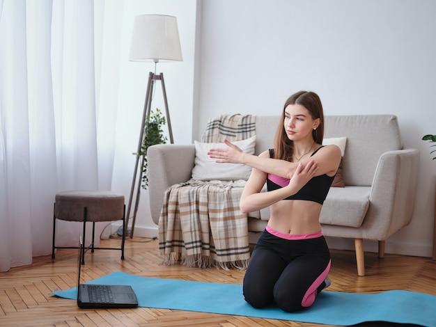 La fille fait des exercices à la maison dans le salon.