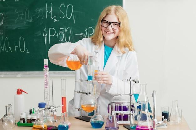 Fille fait une expérience chimique dans une leçon de chimie