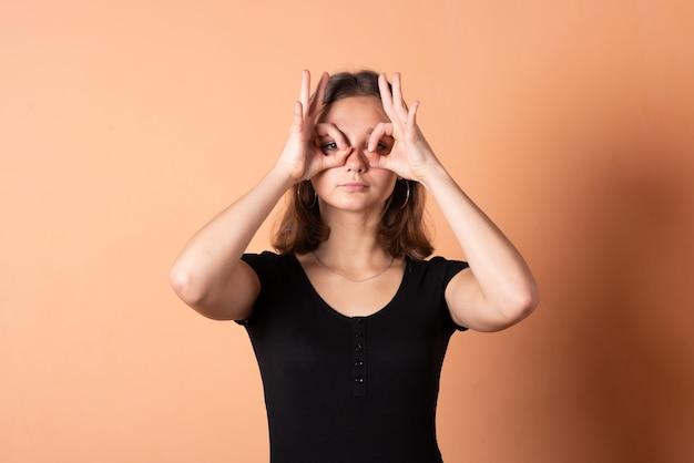 Fille fait des lunettes avec les mains, sur un fond orange clair. pour n'importe quel but.