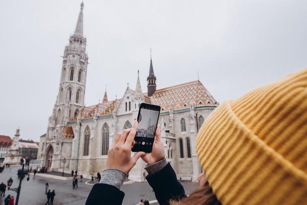 Fille fait une photo sur le téléphone. fille au chapeau d'hiver jaune décolle.