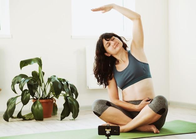 Une fille fait une séance d'entraînement à la maison - une fille est assise sur le sol et répète les exercices pour une séance d'entraînement via un lien vidéo