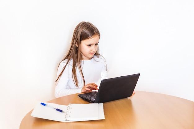 Fille fait ses devoirs à l'aide d'un ordinateur portable