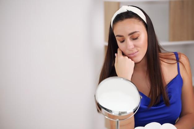 Une fille fait des soins de la peau, à la maison, en chemise de nuit