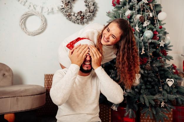 Fille fait une surprise du nouvel an à son petit ami concept et décorations de noël