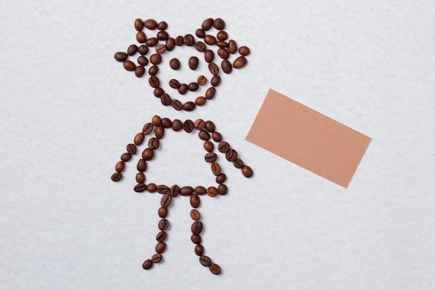 Fille faite de grains de café et de papier vierge pour copyspace. surface isolée blanche.