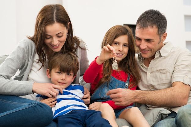 Fille avec famille montrant la clé de la maison