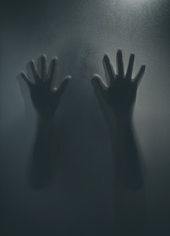 Fille fantôme d'horreur derrière le verre mat en noir et blanc. concept du festival d'halloween