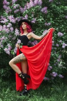 Fille fashion aux cheveux rouges et au grand chapeau, portrait de printemps en lilas