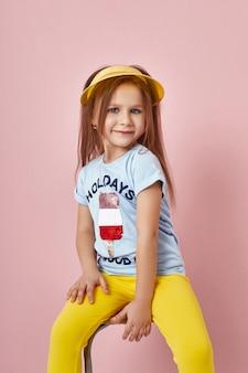 Fille fashion dans des vêtements élégants sur le mur de couleur. vêtements lumineux d'automne sur les enfants